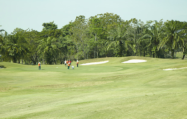 caddies on green at pattaya country club, pattaya