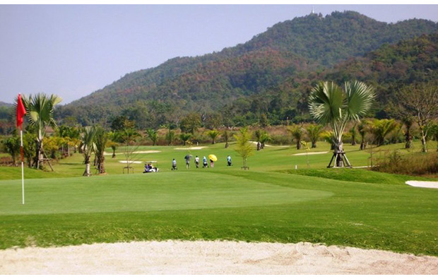 golfers at happy city golf resort, chiang rai, thailand